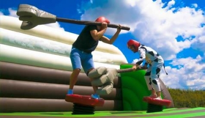 Two guys fighting on a bouncy castle